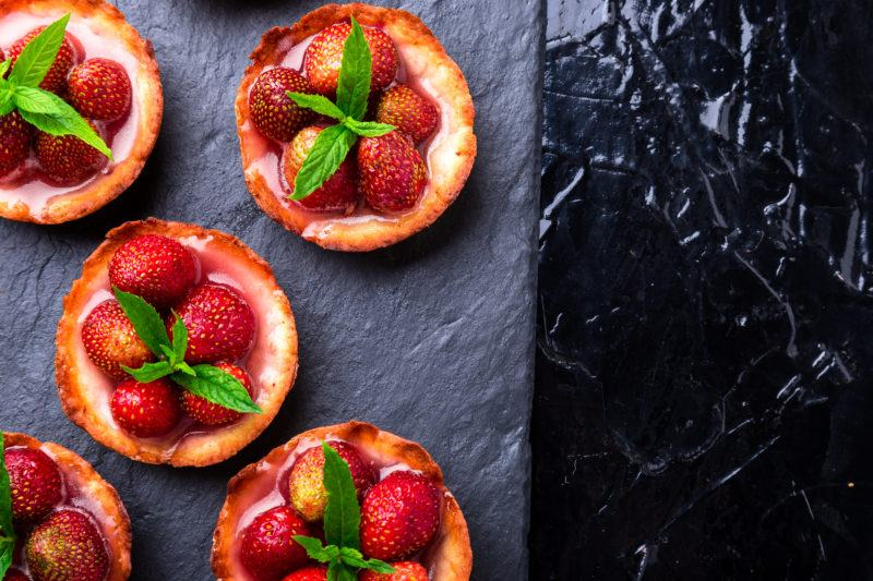 Homemade strawberries tarts on slate plate, black background. Top view.