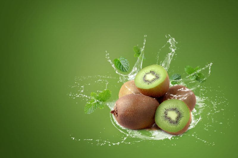 Water splashing on kiwi fruit and half kiwi